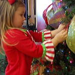Three-year-old Graci Holder, from Hixson, Tenn., hangs an ornament on the tree. Graci is a sibling of a patient at Children's Hospital.
